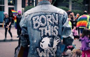 """man in jean jacket with """"born this way"""" on the back. People with rainbow flags in background."""