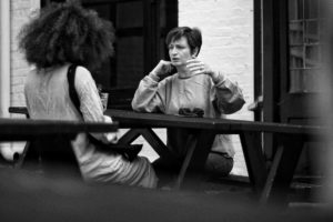 two women at a table outside talking